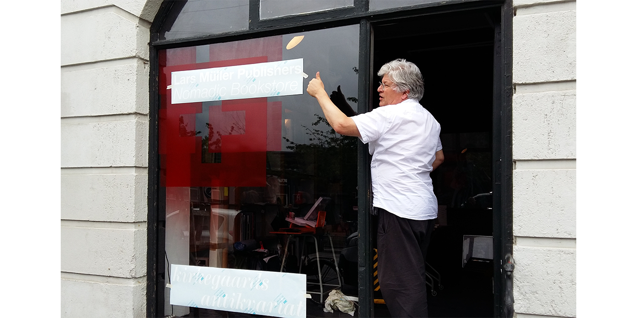 Lars supervising the attachment of the new sign on Tommy's shop window